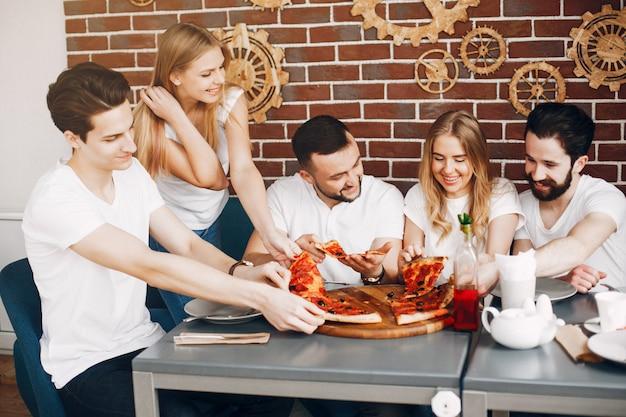 Lindos amigos en una cafetería comiendo una pizza Foto gratis