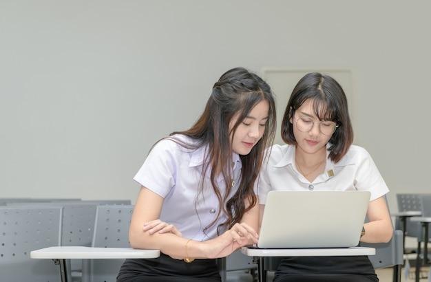 Lindos estudiantes en uniforme trabajando con laptop Foto Premium