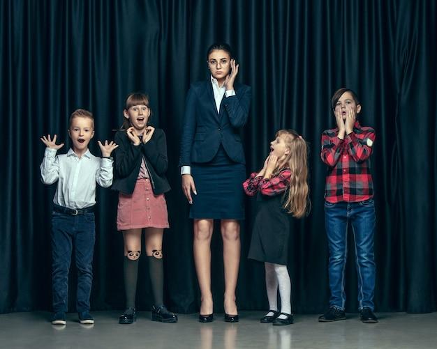 Lindos niños con estilo sobre fondo oscuro de estudio. las hermosas adolescentes y el niño parados juntos Foto gratis