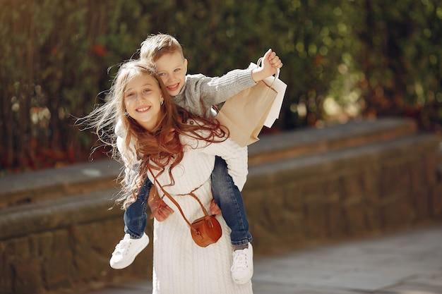 Lindos niños pequeños con bolsa de compras en una ciudad Foto gratis
