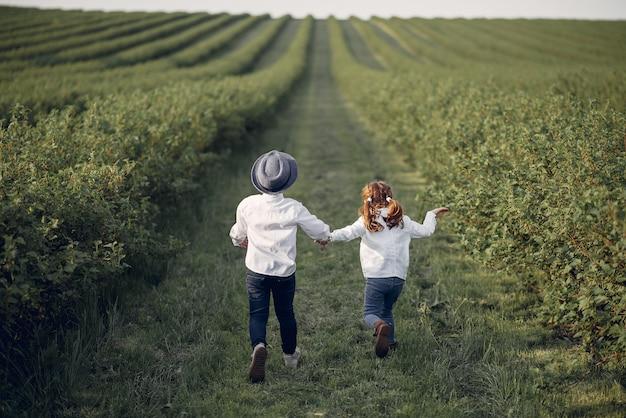 Lindos niños pequeños en un campo de primavera Foto gratis