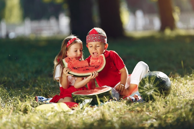 Lindos niños pequeños con sandías en un parque Foto gratis