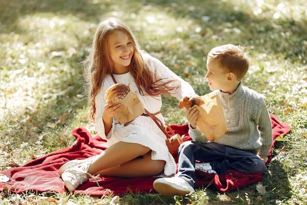 Lindos niños pequeños sentados en un parque con pan Foto gratis