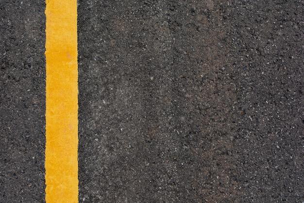 Línea amarilla sobre fondo de carretera de asfalto negro con espacio de copia Foto Premium
