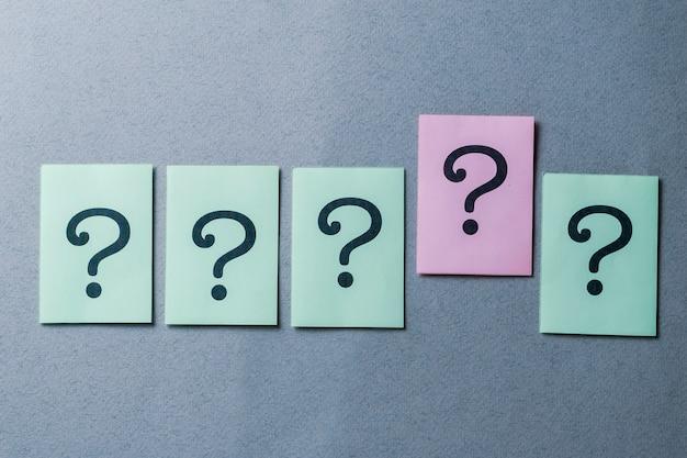 Línea de cinco signos de interrogación impresos en gris Foto Premium