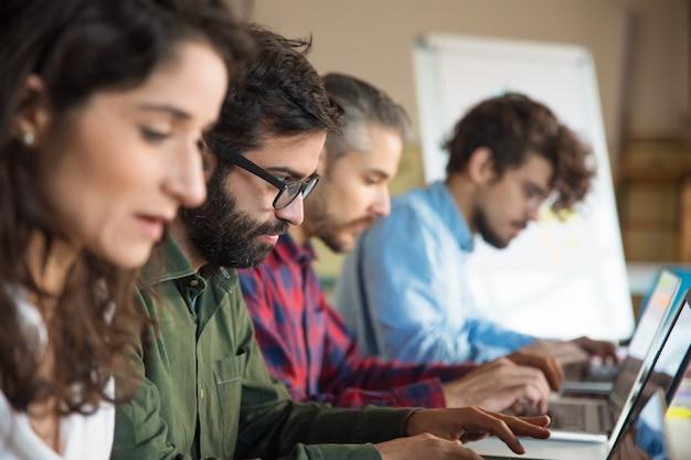 Línea de compañeros de trabajo que usan computadoras portátiles en la sala de entrenamiento o clase Foto gratis