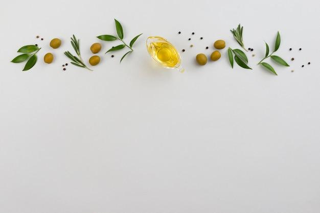 Línea de hojas y aceitunas con taza de aceite. Foto Premium