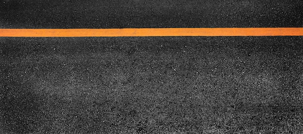 Línea de pintura amarilla sobre asfalto negro. fondo de transporte espacial Foto Premium