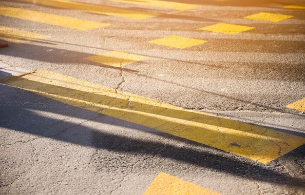 Línea de pintura amarilla en la textura de la superficie de la carretera de asfalto negro Foto gratis