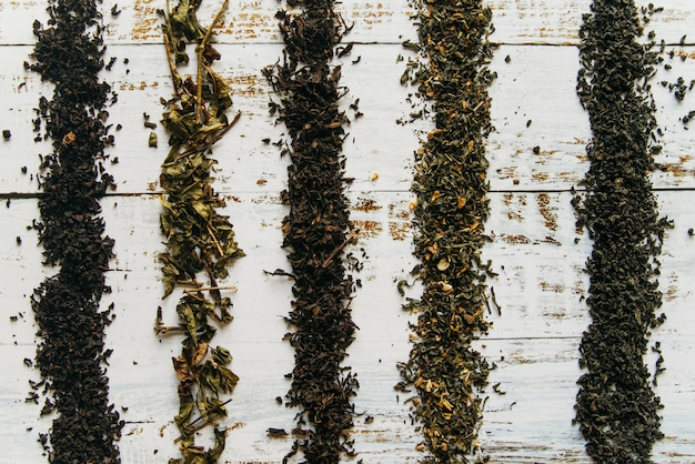 Líneas hechas con hierbas secas de té en el escritorio blanco Foto gratis