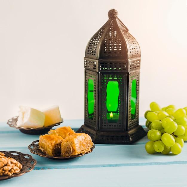 Linterna cerca de uva verde con baklava y delicias turcas en platillos Foto gratis