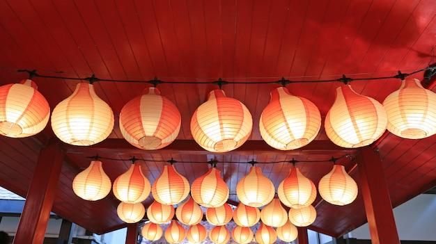Linternas japonesas asiáticas rojo-blancas de papel en fila que brillan intensamente. Foto Premium