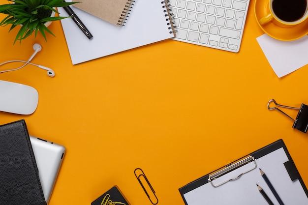 Lío de fondo amarillo en su teclado de escritorio, ratón, taza de café Foto Premium