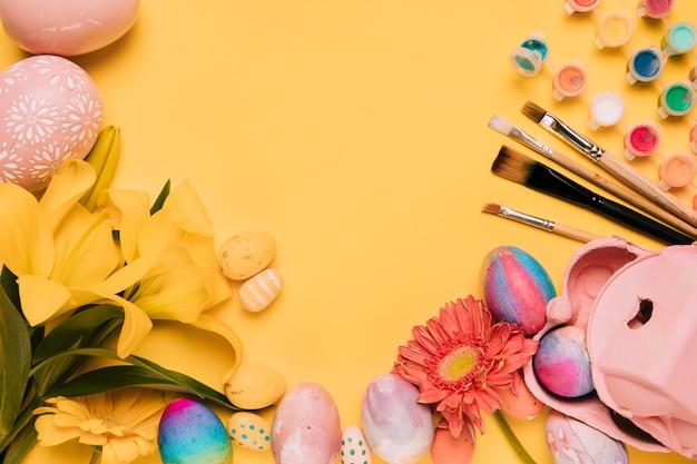 Lirio; flor de gerbera; cepillo de pintura; pintura de acuarela; con huevos de pascua sobre fondo amarillo Foto gratis