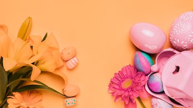 Lirio fresco flores de gerbera con huevos de pascua sobre fondo amarillo Foto gratis