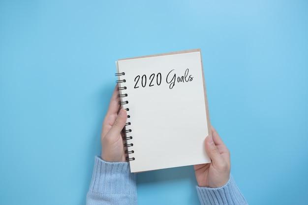 Lista de objetivos de año nuevo 2020 con cuaderno sobre fondo azul, estilo plano. concepto de planificación. Foto Premium