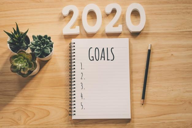 Lista de objetivos de año nuevo 2020. mesa de escritorio de oficina con cuadernos y pancil con planta de maceta. Foto Premium