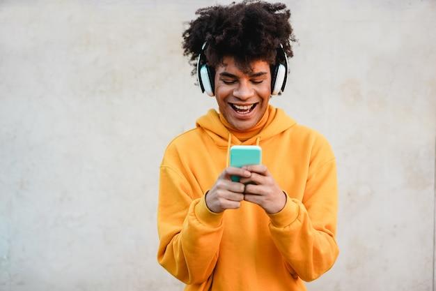 Lista de reproducción de música de chico feliz del milenio africano con aplicación de teléfono inteligente al aire libre - hombre joven que se divierte con las tendencias tecnológicas - tecnología, generación z y concepto elegante Foto Premium
