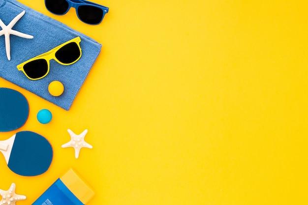 Listo para unas vacaciones de playa en el mar: toalla, gafas de sol y crema solar Foto gratis