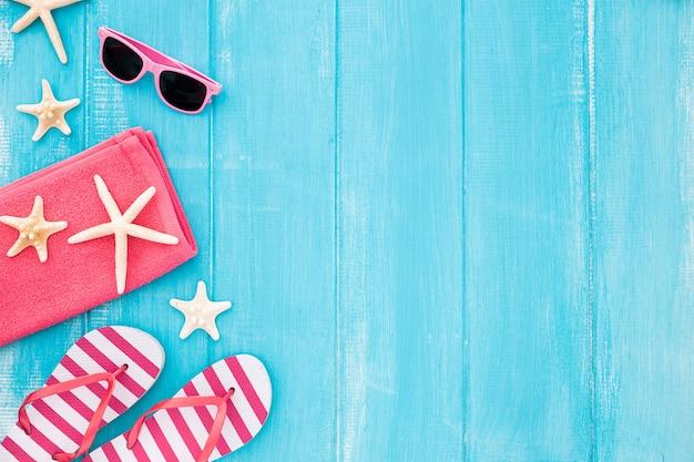 Listo para unas vacaciones de playa en el mar: toalla, gafas de sol y estrellas de mar Foto gratis