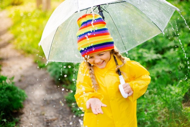 Little blonde girl smiles salta sobre charcos en primavera en un impermeable amarillo y botas de goma con paraguas Foto Premium