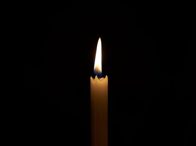 Llama de la vela en el cuarto oscuro. la luz de los medios ...