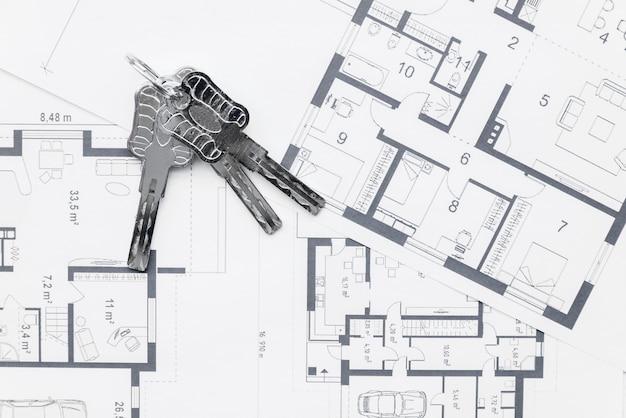Llaves de casa en planos arquitectónicos. Foto gratis