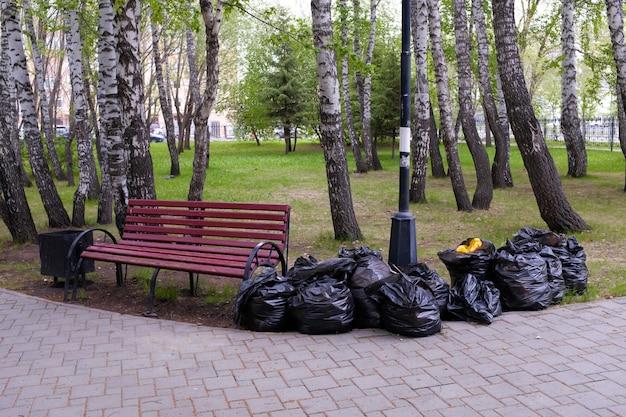 Lleno de bolsas plásticas negras de basura en la naturaleza, en un parque público, a lo largo de la carretera, al lado del banco. limpieza de primavera o otoño de la ciudad del follaje del año pasado. protección del medio ambiente Foto Premium