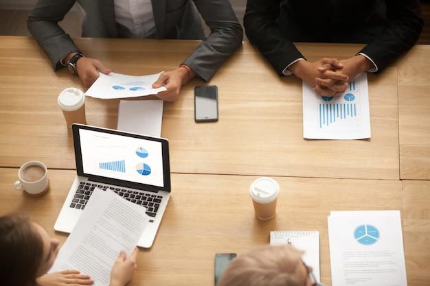 Lluvia de ideas del equipo de negocios que analiza informe de las estadísticas en la reunión, vista superior Foto gratis