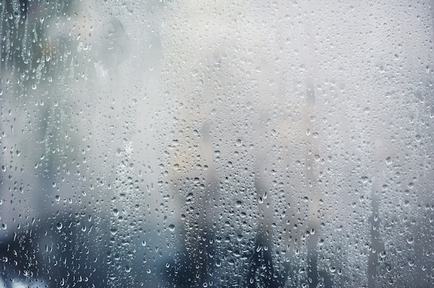 Lluvioso, gotas de lluvia en la ventana, telón de fondo de la temporada de otoño Foto Premium