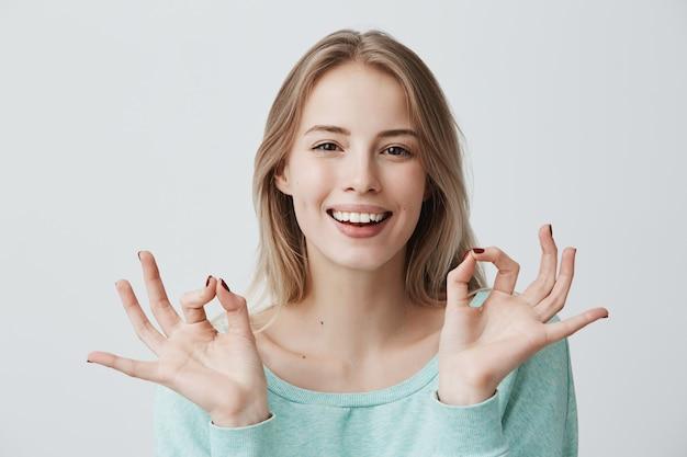 Lo estoy haciendo genial. me alegro feliz joven mujer rubia en suéter azul  sonriendo ampliamente y