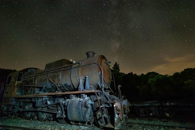 Locomotora antigua con vía láctea por encima de ella. Foto Premium
