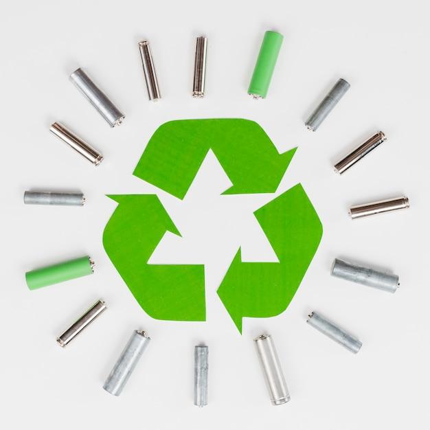 Logo reciclado rodeado de basureros. Foto gratis