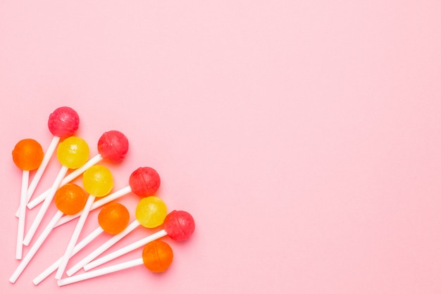 Lollipop de color rosa pastel con dulces de color rosa, naranja y amarillo. composición minimalista. Foto Premium