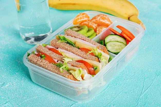 Lonchera escolar con sandwich, verduras, agua y frutas en la mesa. Foto gratis