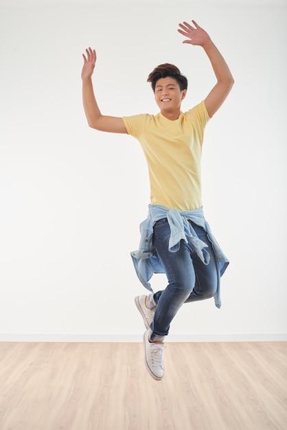 Longitud total de alegre chico asiático bailando Foto gratis