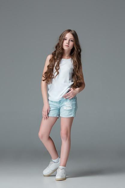 Longitud Total De Joven Delgada Mujer En Pantalones Cortos De Mezclilla Sobre Fondo Gris Foto Gratis