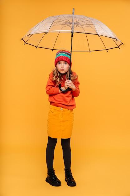 Longitud total jovencita en suéter y sombrero escondiéndose detrás del paraguas y mirando a la cámara sobre naranja Foto gratis
