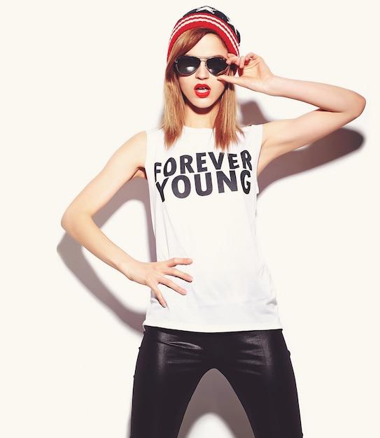 Look de alta moda modelo glamour elegante y bella mujer joven con labios rojos en tela hipster en gafas de sol en gorro colorido Foto gratis