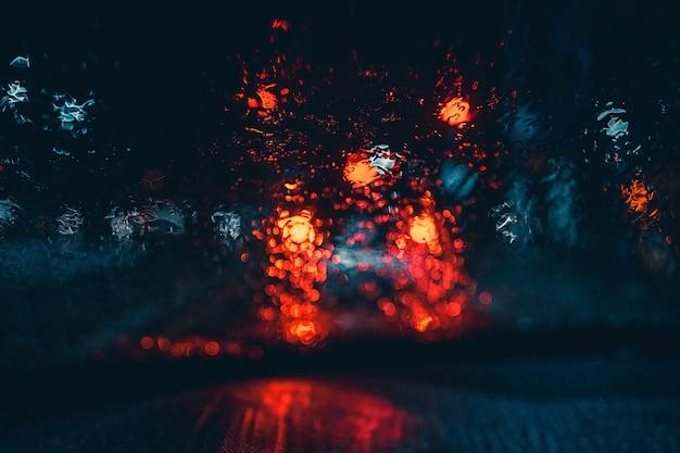 Luces borrosas del automóvil mojado desde el interior de un automóvil Foto gratis