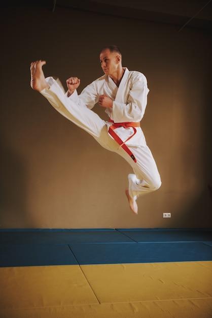Luchador de artes marciales en blanco saltando con patada Foto Premium