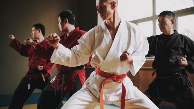 Luchadores con cinturones rojos y negros haciendo posturas de lucha. Foto Premium