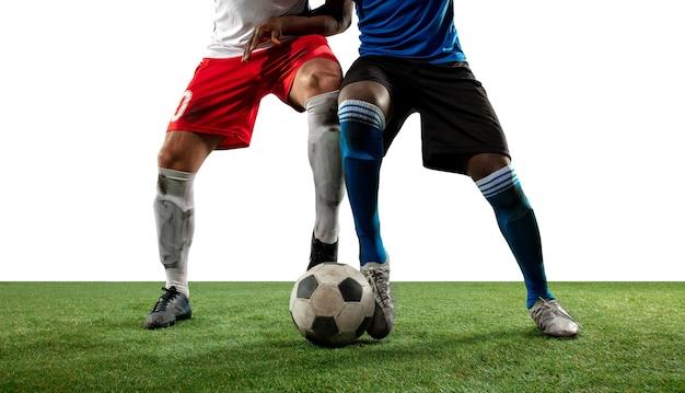 Luchando. cerrar las piernas del fútbol profesional, jugadores de fútbol que luchan por la pelota en el campo aislado en la pared blanca. concepto de acción, movimiento, emoción de alta tensión durante el juego. imagen recortada. Foto gratis