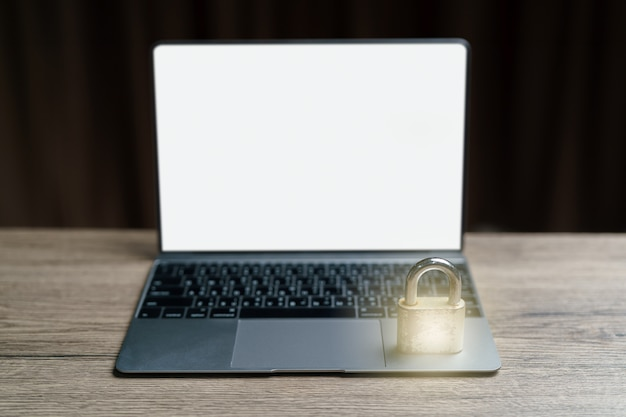 El lugar de la llave maestra dorada en la computadora portátil es un concepto para bloquear datos. Foto Premium