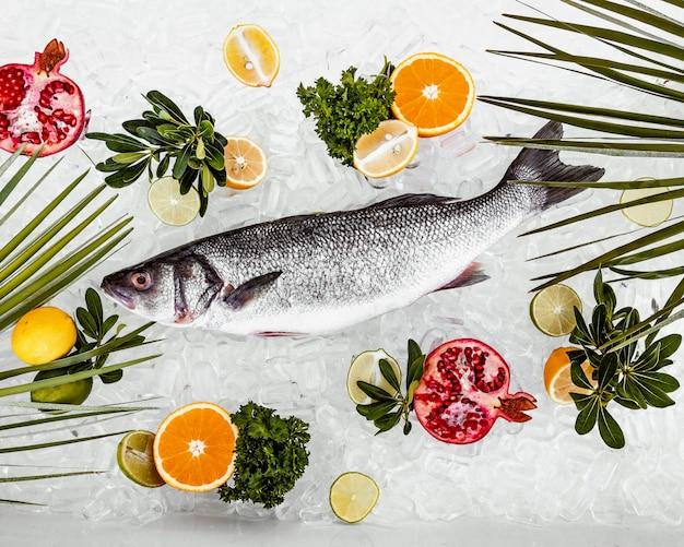 Lugar de pescado crudo en hielo rodeado de rodajas de frutas Foto gratis