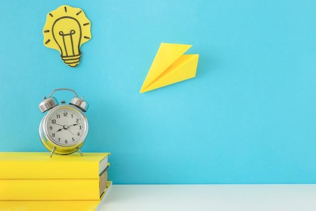 Lugar de trabajo creativo con cuadernos amarillos y reloj despertador Foto gratis