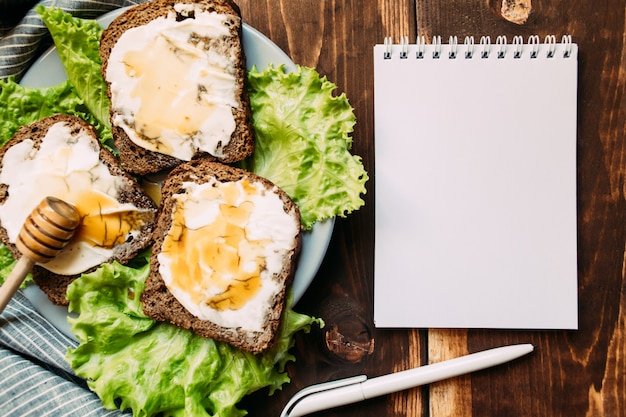 Lugar de trabajo con cuaderno en blanco, bolígrafo y bocadillos Foto Premium