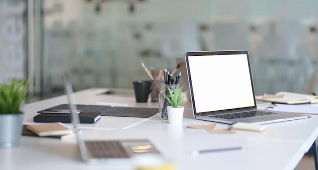 Lugar de trabajo del diseñador con laptop abierta con pantalla en blanco Foto Premium