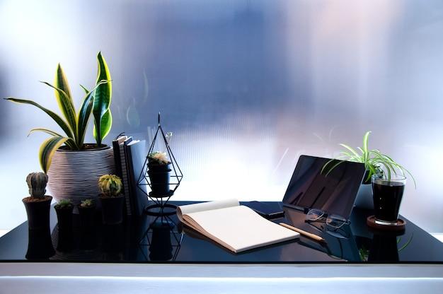 Lugar de trabajo con ipad moderno en mesa de cristal, pantalla simulada en negro, planta de interior y suministros. Foto Premium