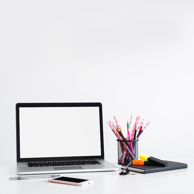 Lugar de trabajo con laptop cerca de la pluma, lápices en lata y teléfono inteligente Foto gratis